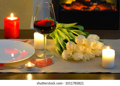 Table in front of fireplace served for romantic Valentine's day dinner