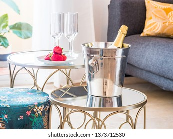 Table with fruit and champagne  in a ice cube in a stylish bright living room with sofa and big window to a terrace with mountain view.Luxury, romantic or celebration lifestyle concept.