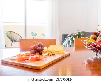 Table with fruit and food in a stylish bright living room with sofa, wooden table, side tables, tv,plants and big window to a terrace with mountain view. Healthy lifestyle concept.