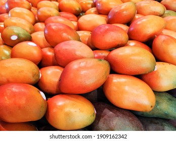 Table with fruits of ripe and green mangoes (Tommy Atkins) in fresh food market.