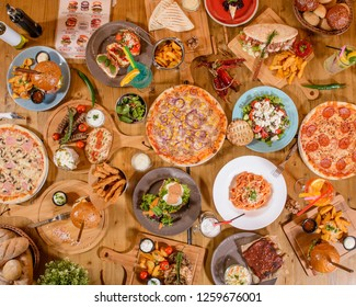 Table full of colorful food top view coffee pizza burger fries pasta