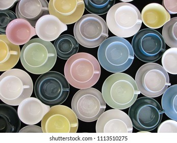 A table full of colorful mid century modern coffee cups and saucers provide a pattern of retro dinnerware