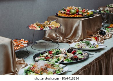 Table full of different interesting and tasty dishes on banquet in restaurant. Variety of plates with salads, assorted meat and cheese, bruschettas and canapes. Food concept.