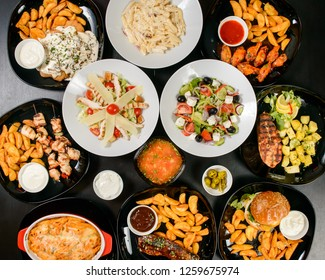 Table full of food flat layout with salad, grill meat, potatoes, caesar salad, pasta, penne al forno