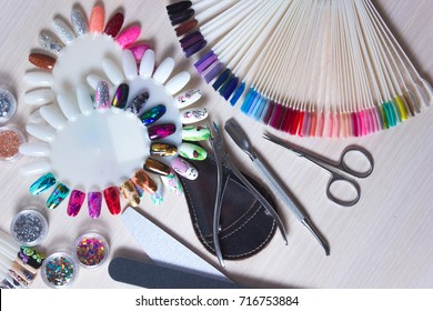 Table full of manicure utensils, manicure tools, nail polish colours on palette. Nails art accessories. Top view