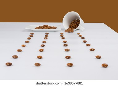 A table full of red beans arranged symetrical with a plate and a cup on the far side