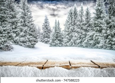 A table full of snowflakes with space for your product advertisement. Winter landscape of trees covered with snow and overcast with blue dramatic sky.