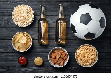 Table full of tasty snacks and beer prepared for watching football on TV, top view
