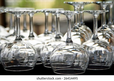 A table full of water and wine glasses under lights for a catered event, reception, and/or party (shallow focus point on foreground glasses).