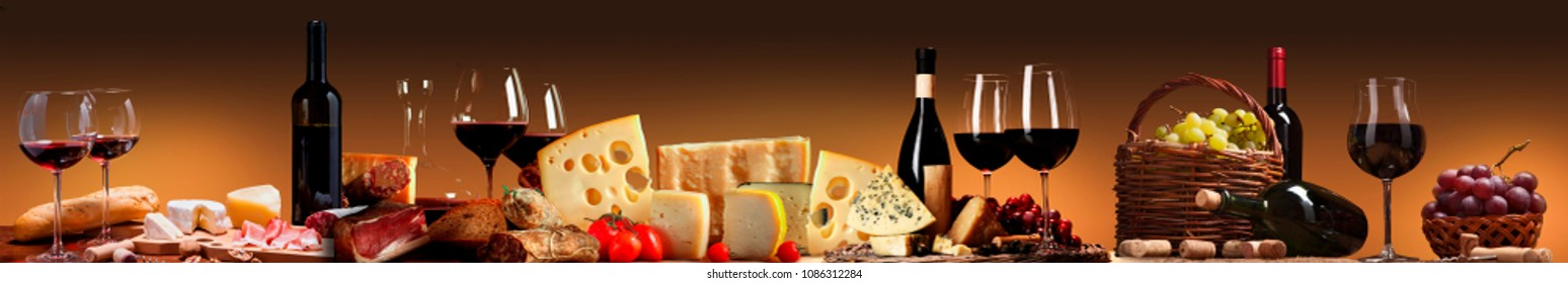 A table full of wine, cheese, sausages and other goodies.