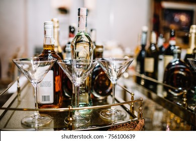 Table   with glasses  and bottles on background. Spread of alcoholic beverages for celebration toasting at wedding reception.