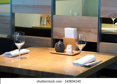 Table with glasses in the cafe with cozy interior.