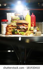 table with hamburger chips sandwich and onion rings