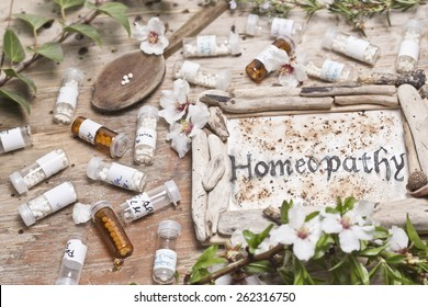 Table with handwritten text  Homeopathy, spoon homeopathy globules and flowers