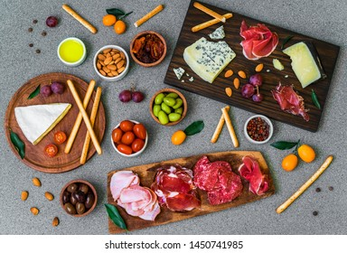 Table of Italian antipasti starters and appetizers with cold meats and cheese delicatessen platter, bread sticks, olives, nuts, and cherry tomatoes