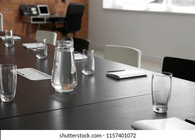 Table with jug of water and glasses prepared for business meeting in conference hall