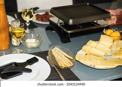 Table in kitchen with food prepared for raclette. Pile of sliced cheese, raclette grill, asparagus, plate, vine, glass, meat and peach in bowl.