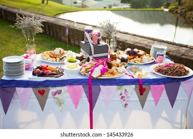 Table laid with fresh bread and condiments at outdoor wedding reception