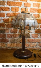 Table lamp with a fancy lampshade at the brick wall