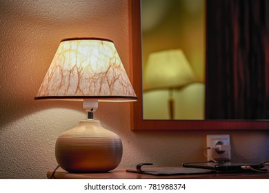 A table lamp next to a mirror in which a floor lamp is reflected.  Soft warm room lighting, semi-darkness.