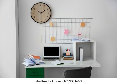 Table with laptop and books near white wall in student's room