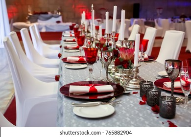 Table layout for a Christmas party. Table setting in red and white for gala dinner or party.