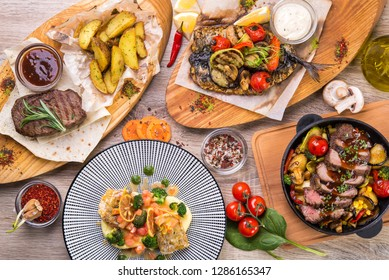 Table lined with dishes steak, roast beef in pan, mackerel with grilled vegetables on a wooden table. top view. flat lay