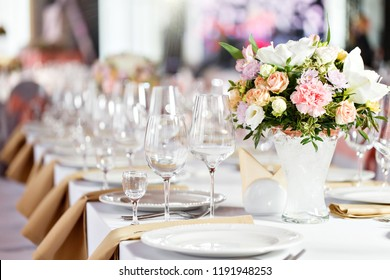 Table at a luxury wedding reception. Beautiful flowers on the table. Serving dishes, glass glasses, waiters work,