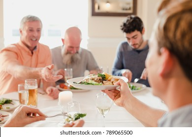 A table of male guests are eating at a wedding dinner together, One of the men is passing his plate to someone else to try.