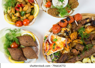 table of middle eastern dishes elegantly presented: kibbeh, falafel, grilled meat