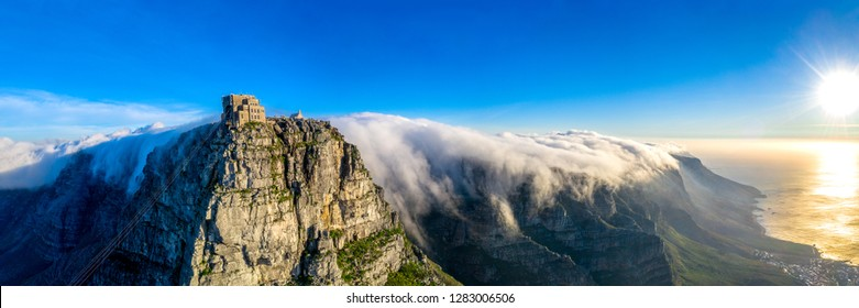 Table Mountain cable way covered in clouds sweeping over the twelve apostles during sunset in Cape Town