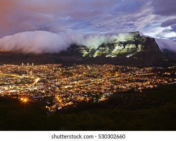 Table mountain illuminated at dusk with the cityscape of Cape Town