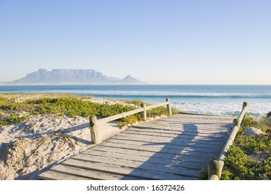 Table Mountain - the world famous landmark in Cape Town, South Africa. Picture taken on a clear Winters day from the Blouberg Strand beach. A wooden bridge over a sanddune is in the foreground.