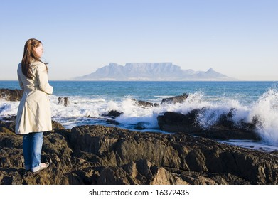 Table Mountain - the world famous landmark in Cape Town, South Africa. Picture taken on a clear Winters day from the Blouberg Strand beach. A girl is standing on some rocks in the foreground.