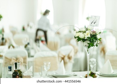 Table number stands in a little bouqet in a high vase