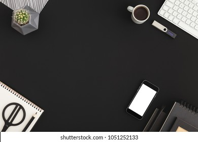 Table office black backround with keyboard, smartphone screen, coffee, plant and notebooks. Black color flat lay.