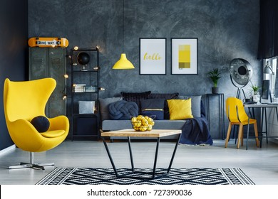 Table on black and white carpet in hygge style living room with designer yellow chair