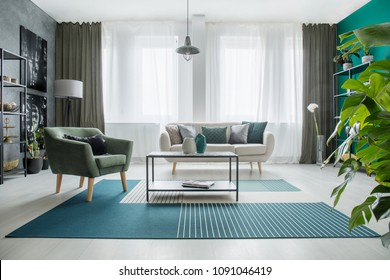Table on carpet next to a green armchair and beige sofa in bright living room interior with plant