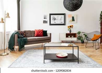 Table on carpet in white apartment interior with sofa, armchair and posters above cabinet. Real photo
