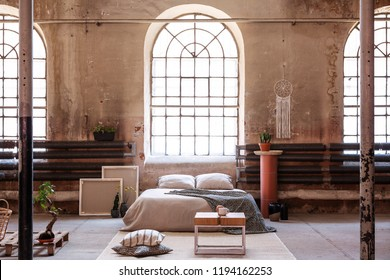 Table on rug in spacious bright bedroom interior with window above cushions on bed. Real photo