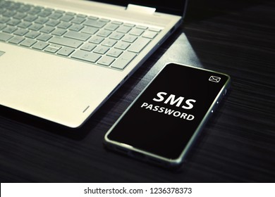 Table with open laptop and black-screened smartphone with white written words SMS password on its display. Concept of linking the work of computer and mobile via sms password entering. One time code
