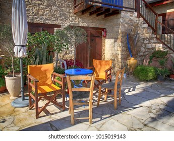 Table and outdoor chairs on terrace with flower pots in beautiful small yard, Cyprus