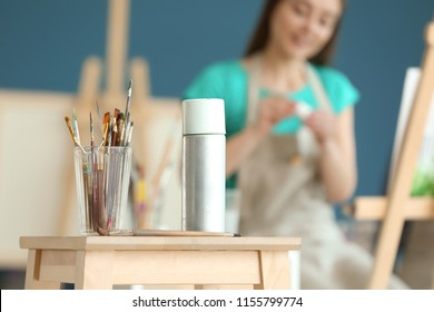 Table with paint tools and aerosol spray in artist's workshop
