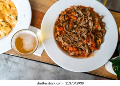 Table with pasta dishes with sauce on a round white plate.