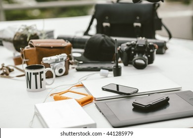 Table with photography gear, camera bags, laptop, external laptop power, external rugged hard drive and drawing tablet.