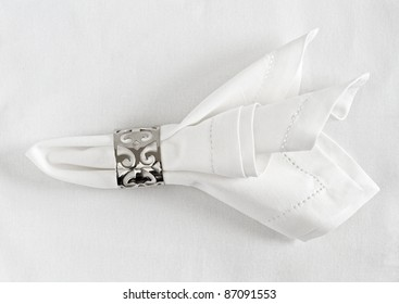 Table place setting of linen napkin and silver napkin ring