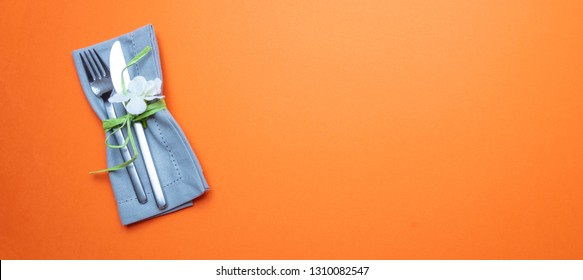 Table place setting in orange color. Gray linen napkin with decoration and cutlery on orange color background, banner, top view,