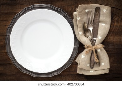 Table place setting with vintage silverware and plate on rustic wooden background