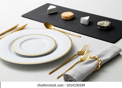 table with plates, cutlery and cheeses