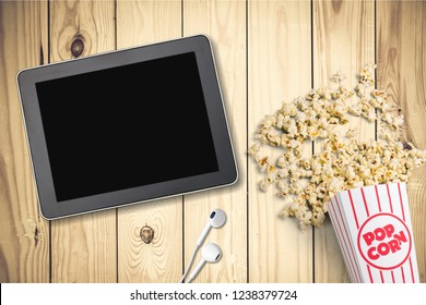 Table with popcorn bottle and Netflix logo on Apple Ipad mini and earphone. Netflix is a global provider of streaming movies and TV series.